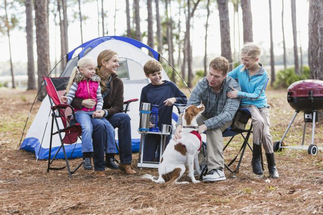 A family with three children and a dog on a camping trip in the woods, sitting by a tent, talking and smiling.  The youngest child, a 5 year old girl, is sitting on mom's lap.  Dad is petting the dog.